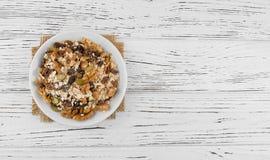 Havremjöl i bunke med frukt, muttrar, russin på en vit tabell Arkivfoto