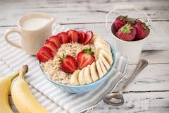 Havremjöl i bunke med jordgubbar och bananer Arkivfoton