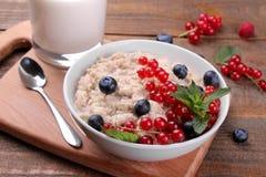 Havremjölet med bär och mjölkar på en brun trätabell Sund mat för frukost fotografering för bildbyråer