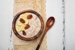 Havremjölhavregröt med banan- och pecannötmuttrar för frukost arkivbild