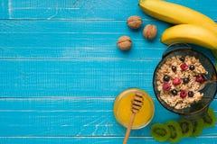 Havremjölhavregröt med bananen, kiwi, muttrar och honung i en bunke med ägget för sund frukost på lantligt trä Royaltyfria Bilder
