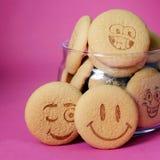 Havremjölkakor i form av en emoticon på en rosa bakgrund Mördegskakakakan för frukost behandla som ett barn kex för mellanmål arkivbild