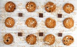 Havremjölkakor och chokladstycken på en vit tappningtabell Royaltyfria Bilder