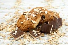 Havremjölkakor och chokladstycken på en vit tappningtabell Royaltyfri Foto