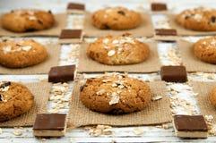 Havremjölkakor och chokladstycken på en vit tappningtabell Royaltyfri Fotografi