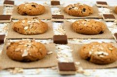 Havremjölkakor och chokladstycken på en vit tappningtabell Arkivfoto