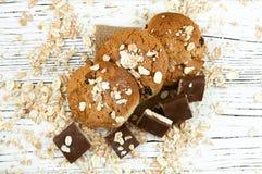 Havremjölkakor och chokladstycken på en vit tappningtabell Arkivfoton