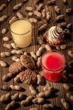 Havremjölkakor och fruktsaft i ett exponeringsglas med glass på en träbakgrund med muttrar 1 Royaltyfri Foto