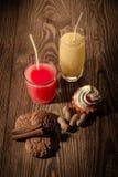Havremjölkakor och fruktsaft i ett exponeringsglas med glass på en träbakgrund med muttrar 1 Arkivfoto