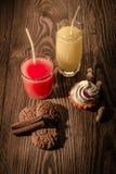 Havremjölkakor och fruktsaft i ett exponeringsglas med glass på en träbakgrund med muttrar 1 Royaltyfri Fotografi