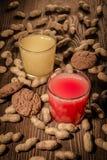 Havremjölkakor och fruktsaft i ett exponeringsglas på en träbakgrund med muttrar 1 Royaltyfri Foto