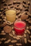 Havremjölkakor och fruktsaft i ett exponeringsglas på en träbakgrund med muttrar 1 Royaltyfri Fotografi