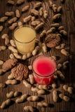 Havremjölkakor och fruktsaft i ett exponeringsglas på en träbakgrund med muttrar 1 Royaltyfria Foton