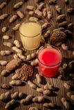 Havremjölkakor och fruktsaft i ett exponeringsglas på en träbakgrund med muttrar 1 Royaltyfri Bild
