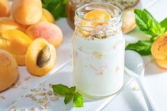 Havremjölmilkshake, smoothie eller yoghurt med den nya aprikons på en vit trätabell arkivfoto