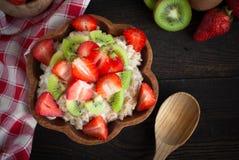Havremjölporrige med jordgubbar och kiwin royaltyfria bilder