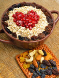 Havremjöl i keramiska platta, sked, russin, kasjuer och mandlar Royaltyfria Foton