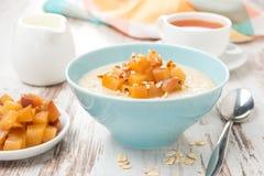 Havremjöl med caramelized persikor, te och yoghurt Arkivbild