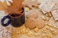 Havremjölkakor, sädes- kex, valnötter och kopp med sidor Fotografering för Bildbyråer