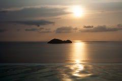 Havsö på horisonten bak oändlighetspöl under härlig solnedgånghimmel arkivbild