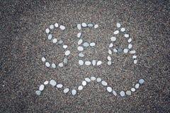 'Havs' ord och vågsymbol på sanden - tonat foto Royaltyfri Bild