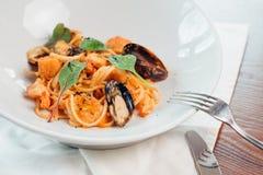 Havs- pasta med musslor och basilika i den vita plattan på trätabellen arkivfoto