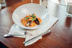 Havs- pasta med musslor och basilika i den vita plattan på trätabellen royaltyfria bilder