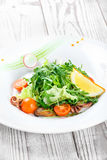 Havs- sallad med musslor, tioarmade bläckfiskar, bläckfisken, arugula, grönsallat och körsbärsröda tomater på träbakgrundsslut up Arkivbilder