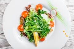 Havs- sallad med musslor, tioarmade bläckfiskar, bläckfisken, arugula, grönsallat och körsbärsröda tomater på träbakgrundsslut up Arkivfoton