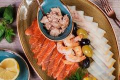 HAVS- UPPLÄGGNINGSFAT Ny torsklever, laxen, räka, skivafiskfilé, dekorerade med örten, citronen och oliv royaltyfri fotografi