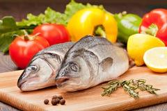 Havsbas som är förberedd till att laga mat på bakgrunden av grönsaker och Arkivbilder