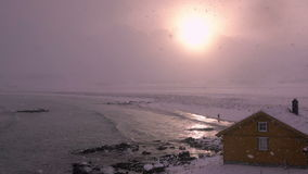 Havsbränning, snöfall, sol och ensam man långsam rörelse stock video