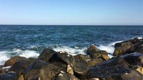 Havsbränningen i fjärden på en molnig dag En liten storm Polenca och port Havsvågtakter på en stor sten framför blåa oklarheter 3 lager videofilmer