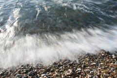 Havschockvågskum på kiselstenstenstranden Arkivfoton