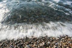 Havschockvågskum på stenstranden Arkivfoto