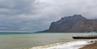 Havsfjärd och bergmassiv Kara-Dag i stormigt väder Fotografering för Bildbyråer