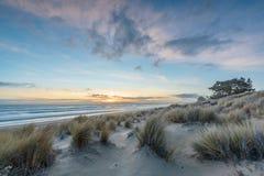 Havsikt av solnedgången med ledande linjer av stranden och vatten arkivfoto