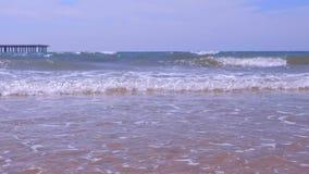 Havskust med långa stora vågor och pir i sandstrand på den soliga dagen arkivfilmer