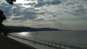 Havskust på en lugna dag och en molnig himmel royaltyfri fotografi