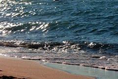 Havskust på natten, ljusa vågor och sammetslen sand Royaltyfri Fotografi