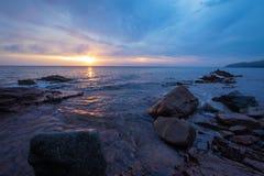 Havskust som är upplyst vid solnedgången Arkivbild
