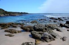 Havskusten med vaggar, blått vatten och klar himmel Arkivbild
