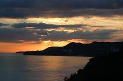 Havslandskap i aftonen, bergen och havet, solnedgång i bergen, moln över havet Arkivfoton