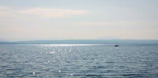 Havslandskap med en fiskebåt på en solig sommardag royaltyfri bild