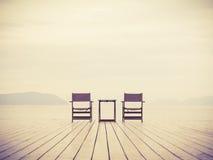 Havslandskapet med två stolar älskar begreppsbakgrund Royaltyfri Foto