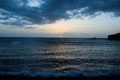 Havsolnedgång, liten bränningvåg, skymning, sjösida, mörk kiselstenkust arkivfoton