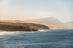 Havsolnedgånglandskap med bergiga kustlinje- och blåtthavvågor Arkivbild