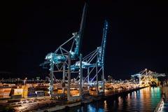 Havsport med kranar, skeppsvarv som är upplyst på natten, Miami, USA royaltyfria bilder