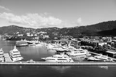 Havsport och stad på solig blå himmel Yachter förtöjde på havspir på berglandskap Lyxigt lopp på fartyget, vatten royaltyfri foto