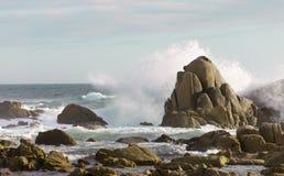 Havsrocken bryter den kraftiga waven Arkivbild